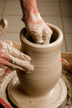 hands of a potter, creating an earthen jar on the circle Stock Photo - 13183836