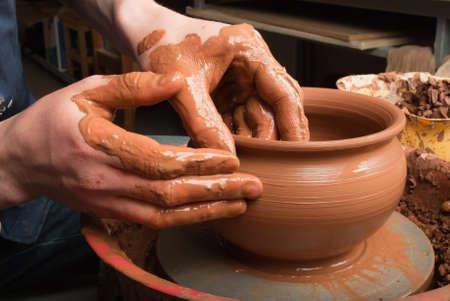 ollas barro: manos de un alfarero, la creaci�n de una vasija de barro en el c�rculo Foto de archivo