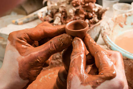 hands of a potter, creating an earthen jar on the circle Stock Photo - 13458920