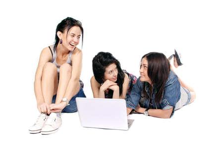 Three girls-students with laptop sitting on white background photo