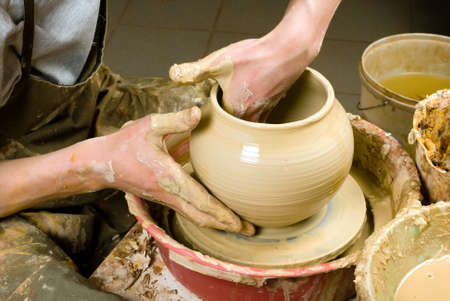 hands of a potter, creating an earthen jar of white clay Stock Photo - 13665913