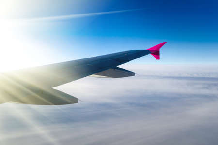 View of jet plane wing with cloud patterns Stock Photo