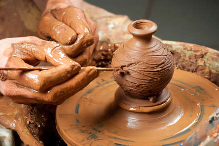 hands of a potter, creating an earthen jar on the circle Stock Photo - 17440958