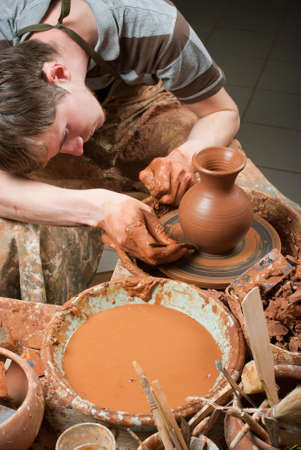 craftswoman: hands of a potter, creating an earthen jar on the circle