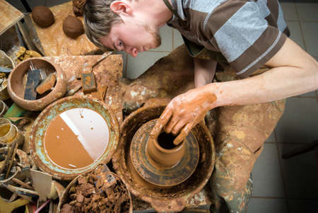 scraping: hands of a potter, creating an earthen jar on the circle