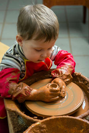 boy potter at work in the studio