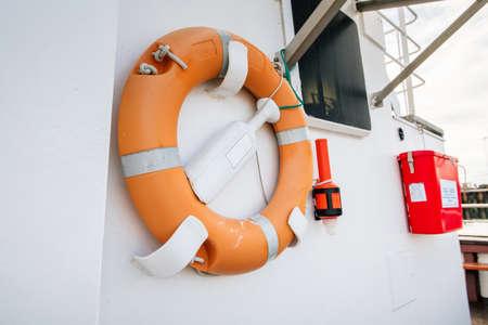 lifeline: Orange lifebuoy on a white yacht side Stock Photo