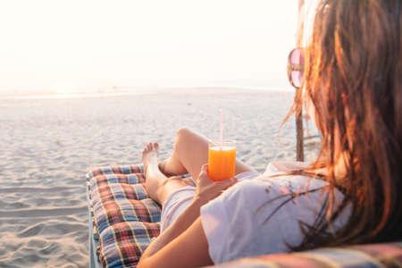 소녀는 해변에서 오렌지 주스 한 잔 함께 스톡 콘텐츠