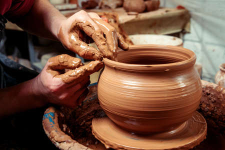 Potter at work. Workshop. Hands of a potter, creating an earthen jar on the circle