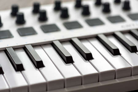White MIDI keyboard with pads and faders. Stock Photo - 90509738