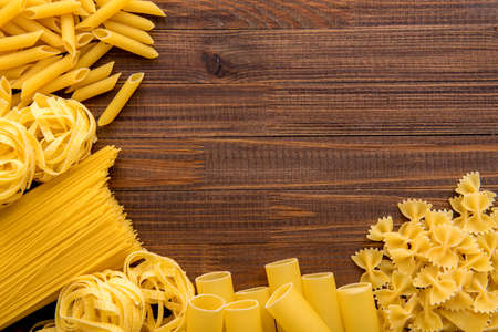 Different kinds of pasta on a wooden background. Farfalle, fettuccine, noodles, fusilli and penne rigate. Tasty Italian cuisine