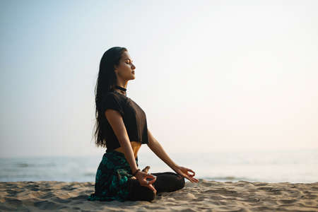 Young healthy woman practicing yoga on the beach at sunset Stockfoto