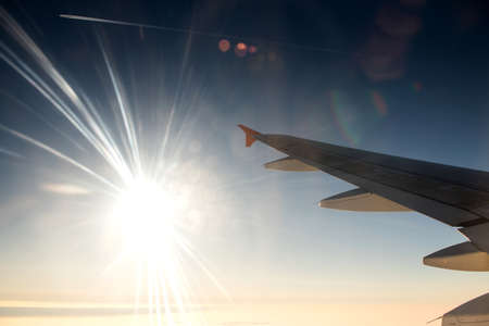 Wing of airplane in with sunrise and blue sky
