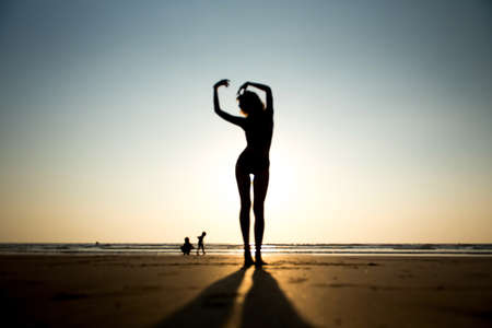 Woman on beach in sunset.