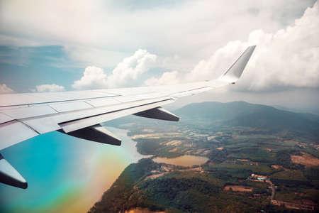 Aile d'avion dans un ciel nuageux avec effet arc-en-ciel. Banque d'images