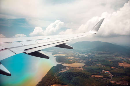 Wing of airplane in cloudy sky with rainbow effect. Reklamní fotografie