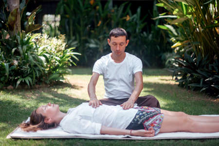 Master makes massage on the background of the garden