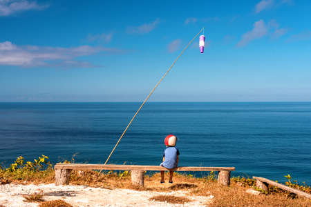 Dreaming boy sits on a bench in a helmet on the background of the sea. View point. Imagens