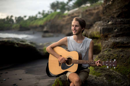Romantic young man playing a guitar on the beach Stock Photo