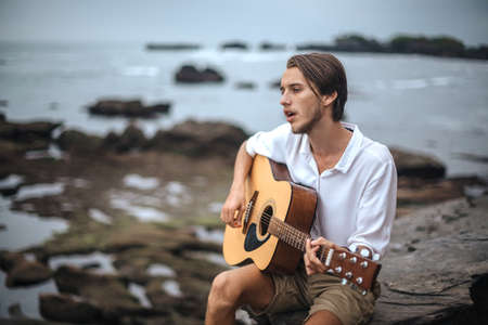 Romantic young man playing a guitar on the beach Stockfoto