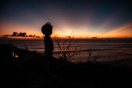 A boy in a helmet looks at the sunset at sea on the viewpoint.