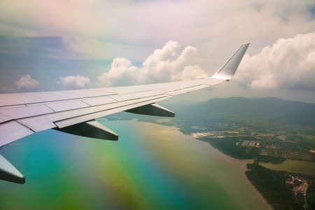 Aile d'avion dans un ciel nuageux avec effet arc-en-ciel.