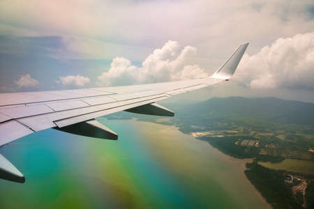 Wing of airplane in cloudy sky with rainbow effect.