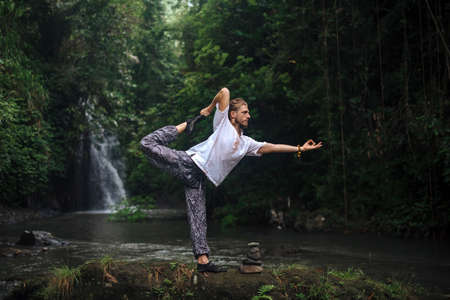 Yoga practice and meditation in nature. Man practicing near river.