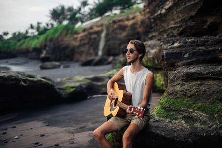 Romantic young man playing a guitar on the beach Reklamní fotografie