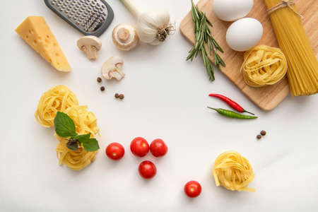 Ingredients for pasta cooking on white background.