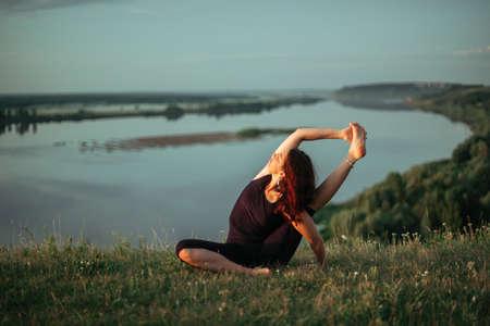 Yoga practice and meditation in nature in sunrise. Woman practicing near big river Kama 免版税图像