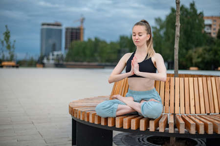 Girl practice yoga and meditation in the city Фото со стока