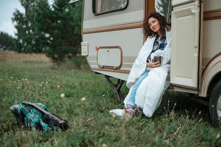 Girl sitting on the camper ladder with a mug in her hands wrapped in a blanket.