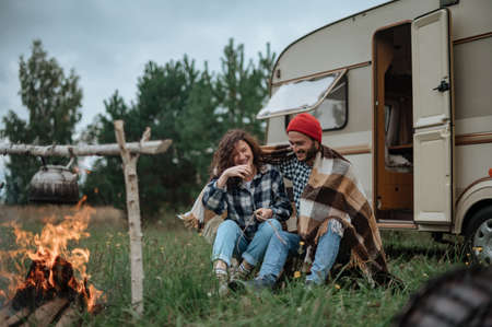 Couple roasting marshmallows on fire near trailer house. Stock fotó