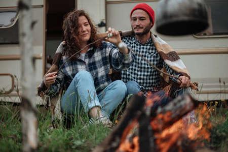 Couple roasting marshmallows on fire near trailer house
