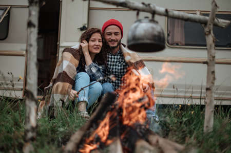 Couple in a checkered plaid roasting marshmallows on fire near the trailer home.