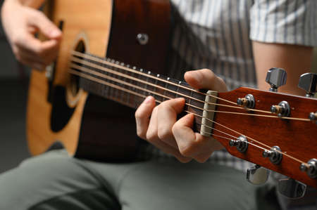 Man playing acoustic guitar, cover for online courses, learning at home. Standard-Bild