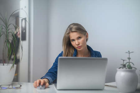 A girl with a laptop is studying at an online school. White room background