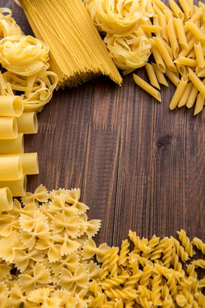 Different kinds of pasta on a wooden background. Farfalle, fettuccine, noodles.