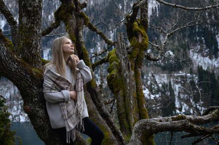 Girl sits on a tree and meditates near lake Ritsa in Abkhazia