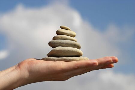 pyramid peak: Pile of stones on the hand, sky and clouds background Stock Photo