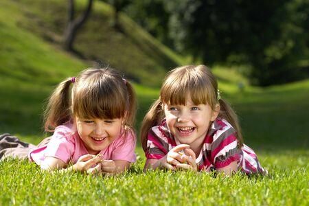 Dwa małe uśmiechnięte dziewczyny leżącej na trawie w parku