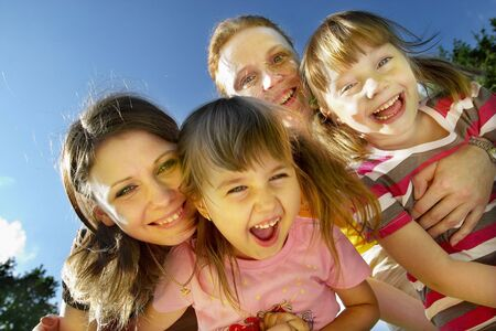 Two mothers with their little daughters smiling and laughing in the park Stock Photo - 5217115