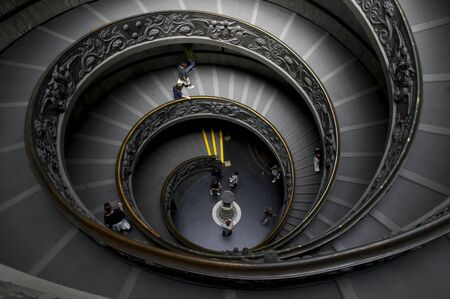 stepping: Spiral stairs in Vatican museum, upper view on a few tourists Stock Photo