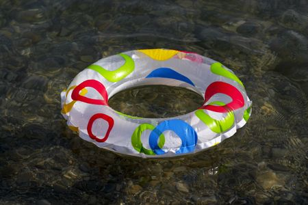 Inflatable ring floating on the sea, transparent clear water Stock Photo