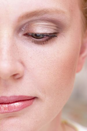 Half of woman face with a makeup macro with one eye half-closed photo