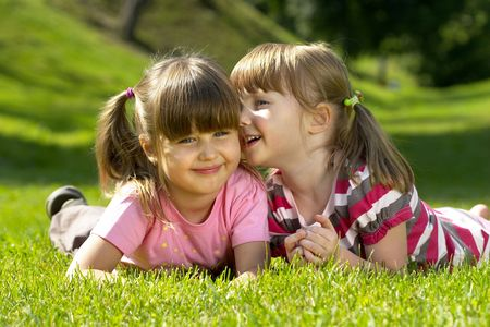 Two little girl lying on the grass in the park. One whispering a secret to another. Stock Photo