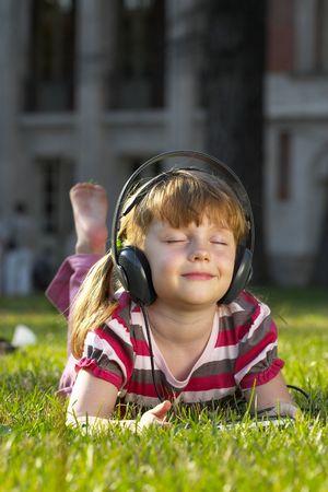 �couter: Petite fille couch�e sur l'herbe dans le parc, �couter de la musique