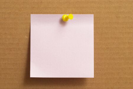 yellow pushpin: Pink sticker note with yellow push-pin on cardboard
