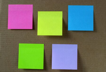 Five colored empty sticker notes on a cardboard photo